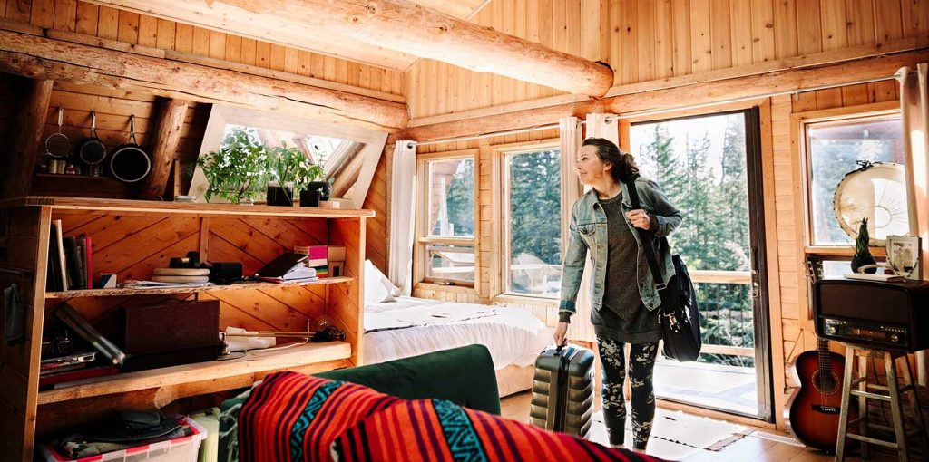 Woman with suitcase arriving at cabin